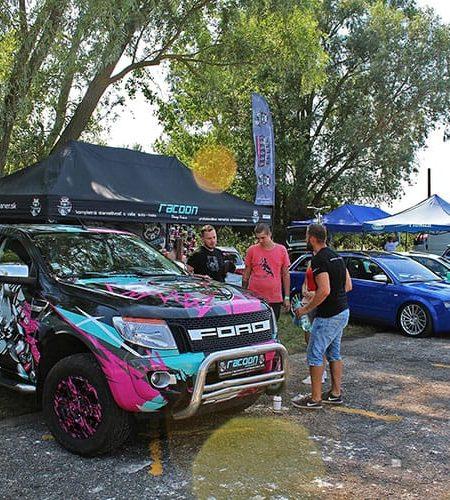 Stánok autokozmetiky Racoon a športové auta v reklamných farbách