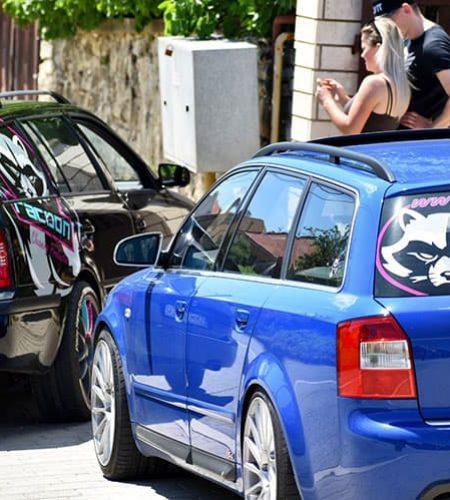 zhovárajúci sa chlap s blondínkou pri zaparkovaných autách modrej audi s4 a škode octavii čiernej farby s reklamným polepom Racoon